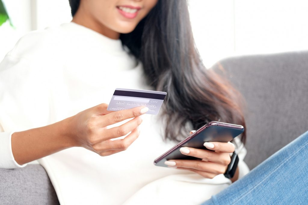 online phone payment by credit card at home, asian woman using m